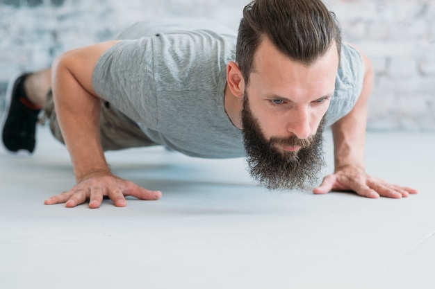 Workout and exercise. man doing push ups. chest muscles and biceps training.