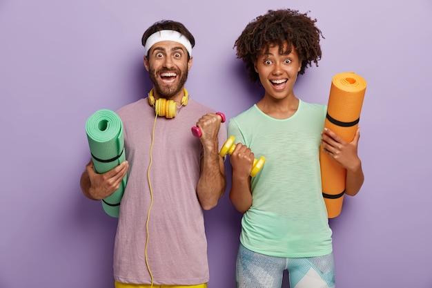 운동, 피트니스 및 스포츠 개념. 쾌활한 혼혈 부부는 운동을하고, 아령으로 팔을 올리고, 매트를 잡고, 체육관에서 훈련합니다. 스포티 한 가족이 함께 스포츠를 시작합니다. 건강한 생활