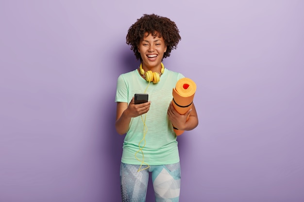 Workout and fitness concept. cheerful dark skinned woman holds mobile phone connected to headphones