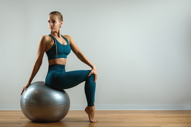 Workout at home. fitness trainer with fitball on a gray background. workouts with various spot inventory. copy space, fitness baren.
