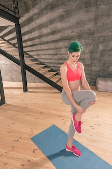 Workout at home. green-haired fit and healthy woman wearing bright pink top working out at home