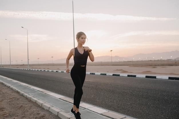 スポーツウェアで魅力的な若い女性の熱帯国の道路で晴れた早朝にトレーニング。ポジティブ、真の感情、健康的なライフスタイル、トレーニング、強力なモデルを表現する