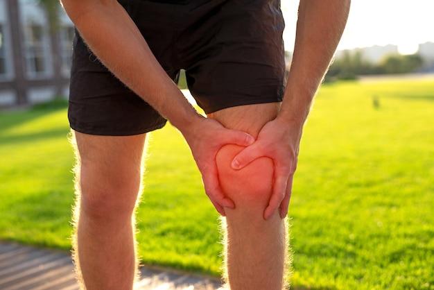 Workout injury concept manは、公園の道路でジョギングしている間、両手を膝につけたままにします。
