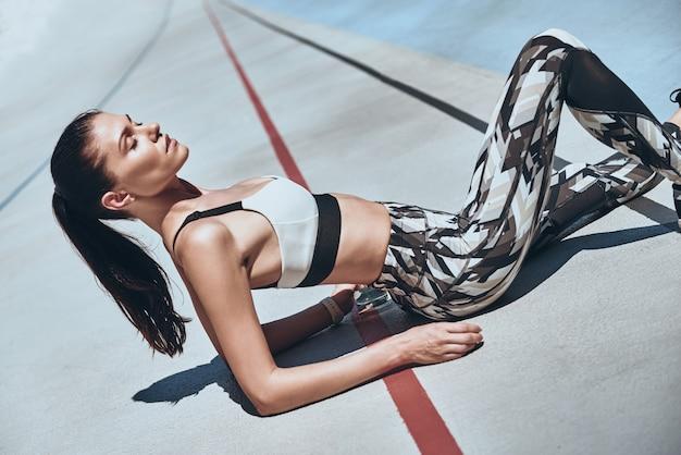 Тренировка окончена. усталая молодая женщина в расслабляющей спортивной одежде