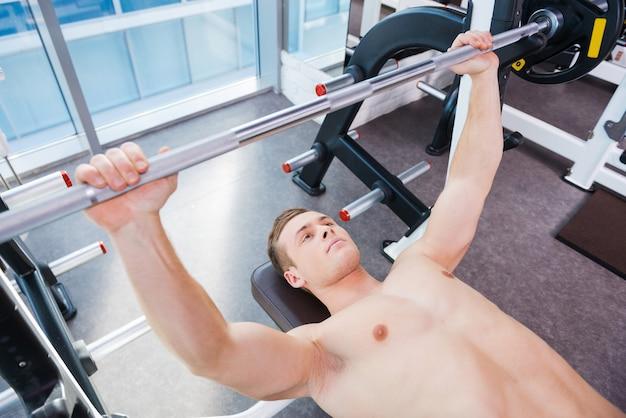 ベンチプレスでのトレーニング。ベンチプレスで働いている自信を持って若い筋肉の男の上面図