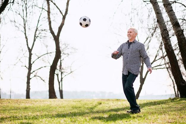 Тренировка на свежем воздухе. энергичный зрелый мужчина тренируется с мячом и играет в парке