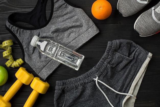 План тренировки с фитнес-едой и оборудованием на темном фоне, вид сверху