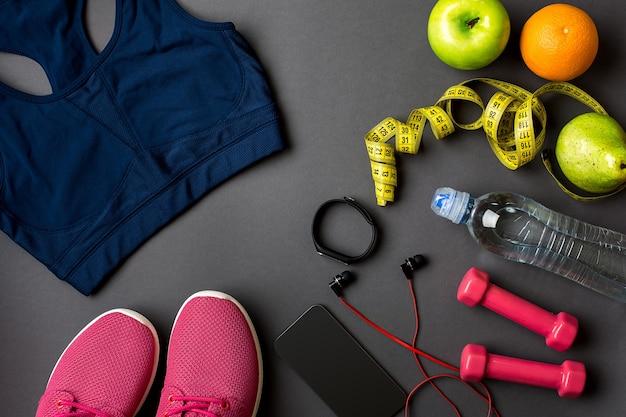 План тренировки с фитнес-едой и оборудованием на сером фоне вид сверху