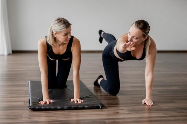 Тренер программы тренировки и клиент делают упражнения фитнеса