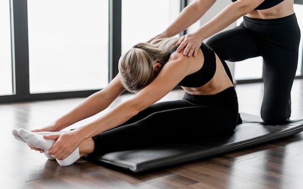 Тренер программы тренировки и клиент, сидя на коврике для йоги