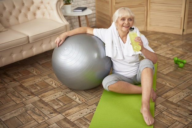 Workout recovery active senior lady drinks water.