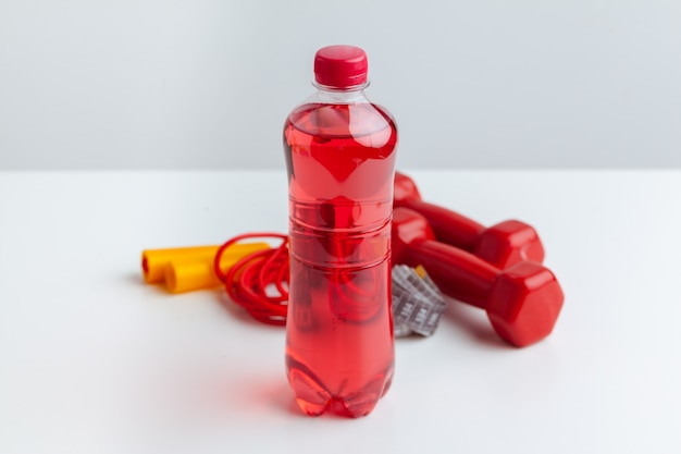 Workout and refreshment concept. sports and health. bottle or fresh water near jump rope