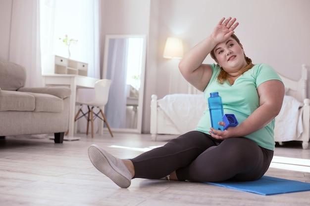 トレーニング休憩。水を飲みながらトレーニング後に休んでいるふっくらとした若い女性