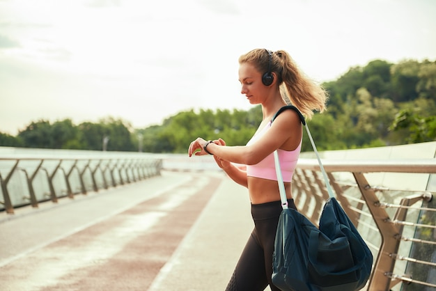 Workout results young sporty woman in headphones carrying bag and looking at her sport bracelet