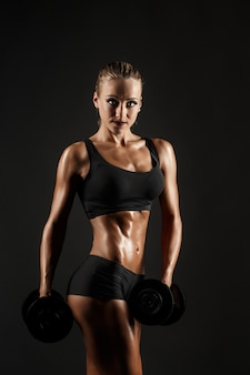 Workout of sexual woman with dumbbells