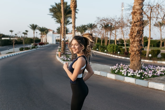 Workout on street with palm trees of attractive young woman in sportwear smiling. expressing posititvity, true emotions, healthy lifestyle, training, sunny morning.