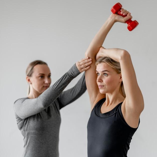 Allenamento con personal trainer e manubri a tiro medio
