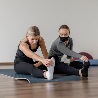Allenamento con personal trainer che allunga le gambe