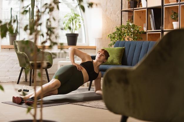 소파로 운동. 집에서 운동하는 젊은 여자