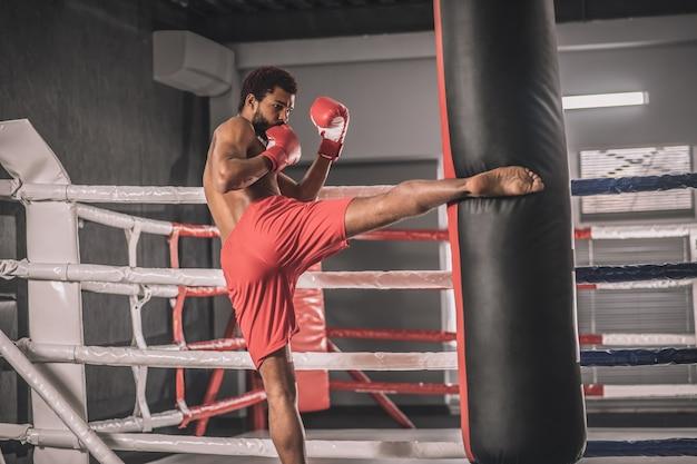 Тренировка. молодой темнокожий кикбоксер пинает ногой мешок с песком