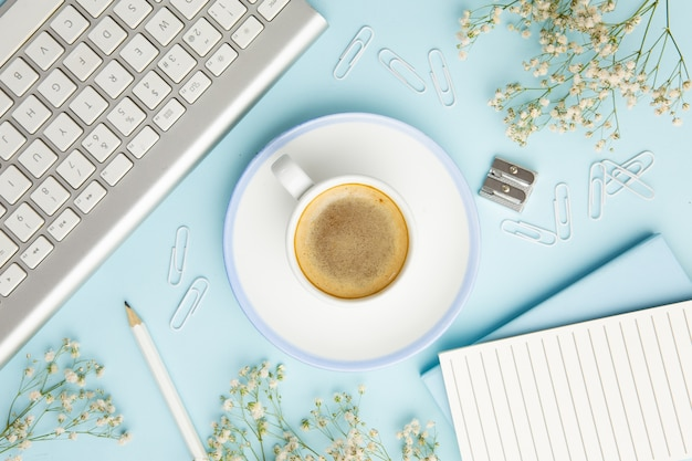 Workplace arrangement on blue background with cup of coffee