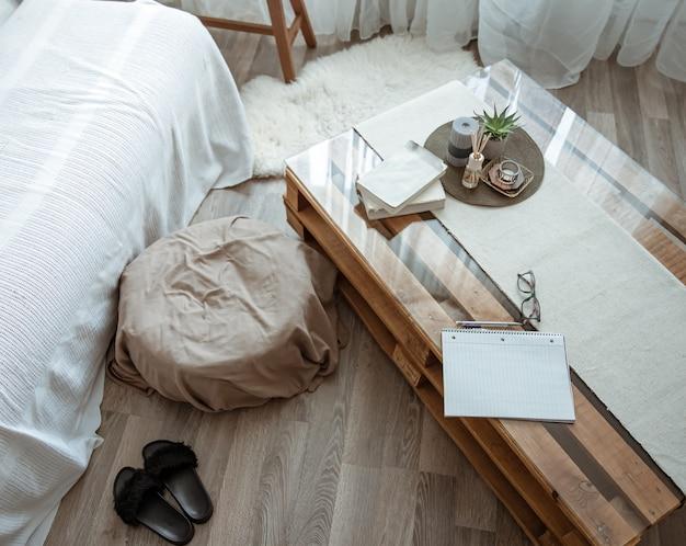 本とノートが置かれたテーブルとその隣に快適なプーフがある自宅の職場。