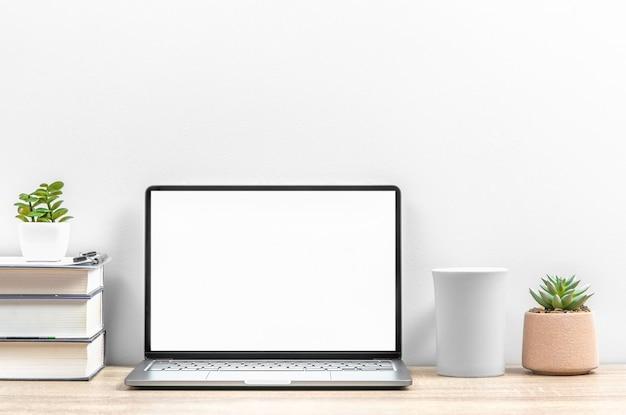 オフィスの職場、テーブルの上にラップトップ、カップ、植物がある家、コピースペース。