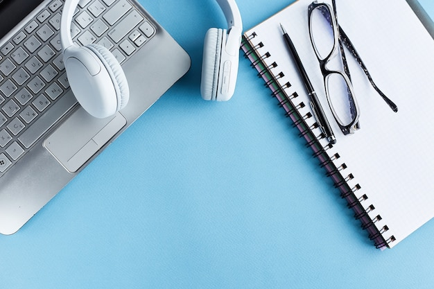 検疫の職場。在宅勤務の職場。自宅からのリモートワーク。白紙と黒のペン、医療用マスク、体温計、ヘッドフォン、ノートパソコン