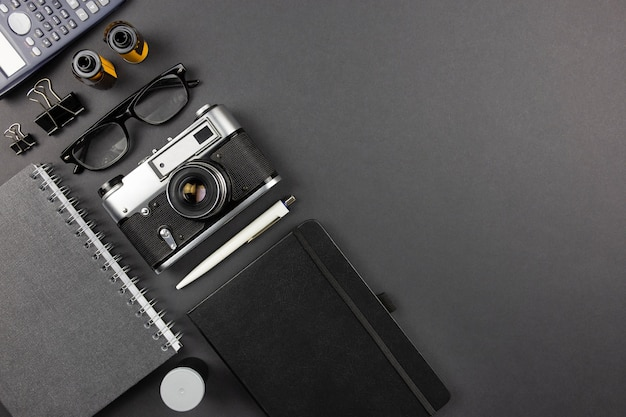 Workplace on black table of a creative designer or photographer with photography equipment