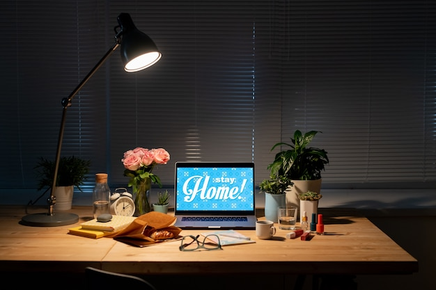 Workplace by window in dark room with laptop, paper sack with croissant, flowers, drinks, cosmetic items, books on table and lamp above