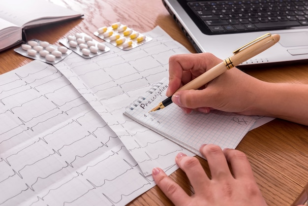 Workplace of cardiologist with patient's cardiogram and prescription