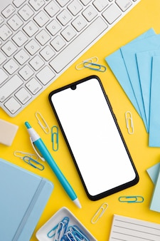 Workplace composition on yellow background with empty phone