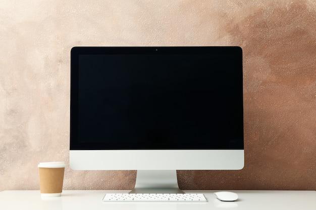 職場。コンピューターと白いテーブルに温かい飲み物のカップ