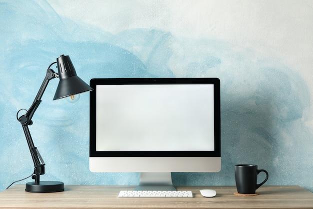 職場。空の画面と木製のテーブルの上にカップを持つコンピューター。ライトブルー