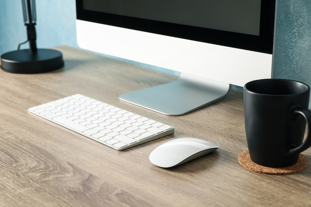 Workplace. computer with empty screen and cup on wooden table, close up