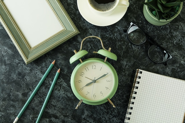 Workplace concept with alarm clock on black smokey