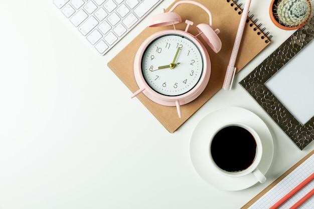 Workplace concept with alarm clock on white surface
