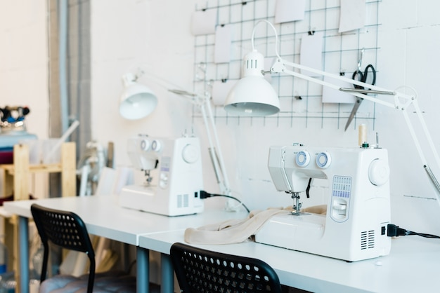 Workplace of contemporary seamstress with chair, desk, lamp and electric sewing machine inside workshop of factory