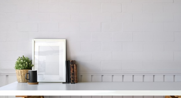 Workplace and copy space, stylish workspace with mockup blank poster, vintage books and house plant.