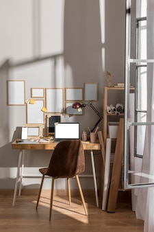 Workplace desk surface with laptop and multiple frames