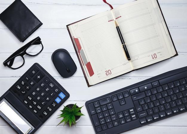 Рабочий стол с клавиатурой, канцелярскими принадлежностями, карандашом, зеленым листом на деревянном столе. рабочий стол офиса. элегантное рабочее место с бизнес-аксессуарами на белом столе с copyspace. креативная плоская планировка фото