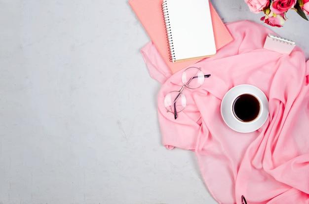 Рабочий стол с блокнотами, бланком, расходными материалами, очками и чашкой кофе