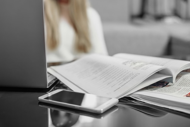 직장. 원격 교육. 노트북, 휴대 전화, 노트북 테이블과 소파의 배경에 젊은 여성 학생의 흐릿한 실루엣