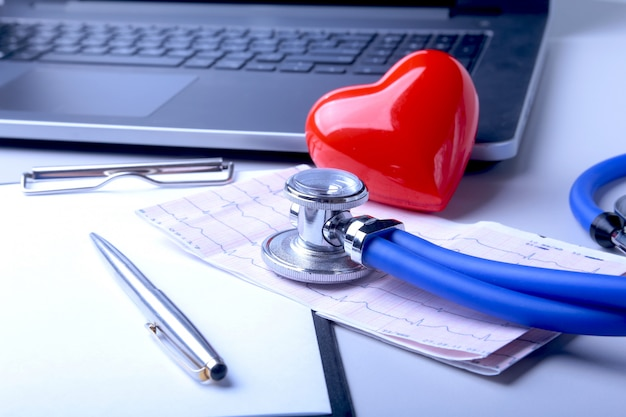 Workplace of doctor with laptop, stethoscope, red heart and rx prescription on white table.