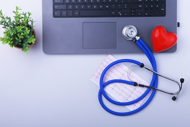 Workplace of doctor with laptop, stethoscope, rx prescription and red heart and notebook on white table.