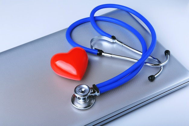 Workplace of doctor with stethoscope, red heart, laptop, rx prescription and notebook on white table