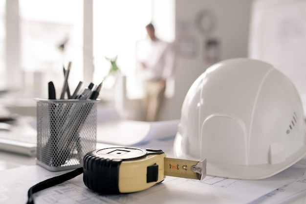 Workplace of engineer with hardhat, measuring tape, bunch of pencils and sketches on background of man