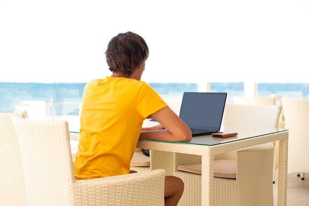 바다가 보이는 카페에서 직장. 카페에서 노트북에서 일하는 남자. 공간을 복사하십시오. 모의.