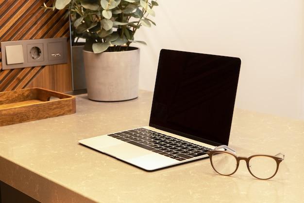 モダンなインテリアのアパートやカフェの職場。テーブルの上でラップトップとグラスを開きます。