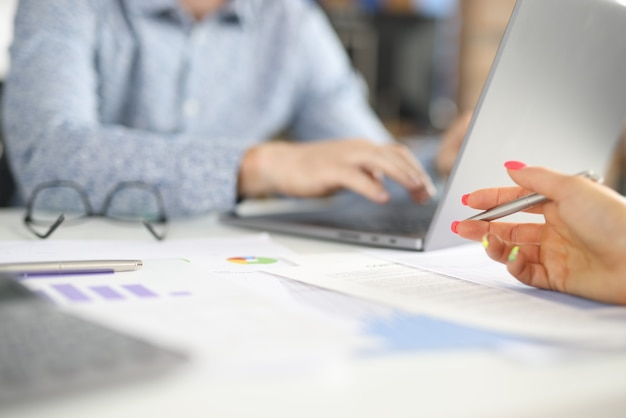 ノートパソコンの後ろに座っているオフィスの人の職場女性の手が商業用グラフの上にペンを保持しています。